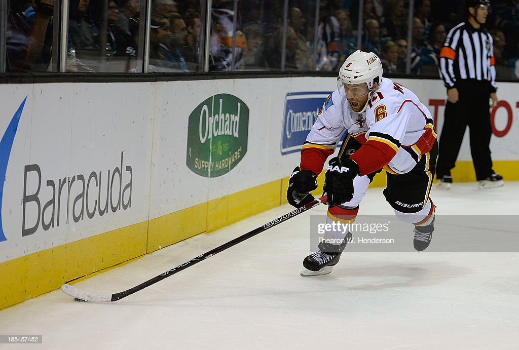 Dennis Wideman #6 of the Calgary Flames skates to gain control of the puck against the San Jose Sharks at SAP Center on October 19, 2013 in San Jose, California.