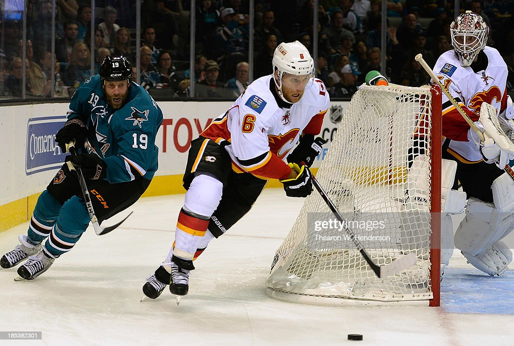 Dennis Wideman #6 of the Calgary Flames skates with control of the puck pursued by Joe Thornton #19 of the San Jose Sharks during the second period at SAP Center on October 19, 2013 in San Jose, California.