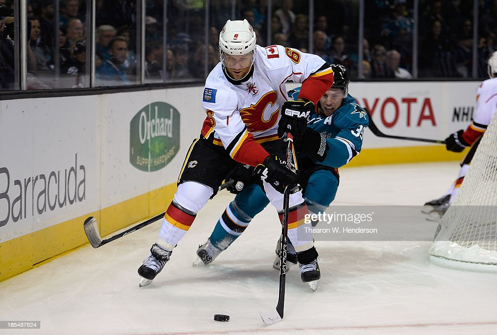 Dennis Wideman #6 of the Calgary Flames skates with control of the puck pursued by Logan Couture #39 of the San Jose Sharks during the second period at SAP Center on October 19, 2013 in San Jose, California.