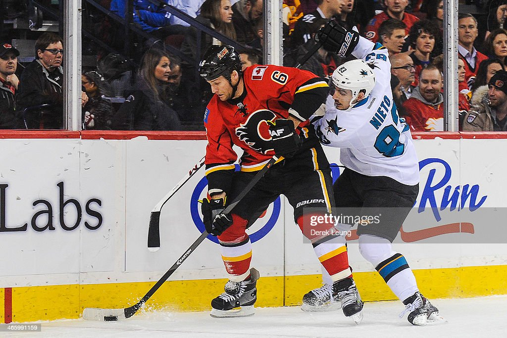 Dennis Wideman #6 of the Calgary Flames skates with the puck as Matt Nieto #83 of the San Jose Sharks tries to check him during an NHL game at Scotiabank Saddledome on January 30, 2014 in Calgary, Alberta, Canada.