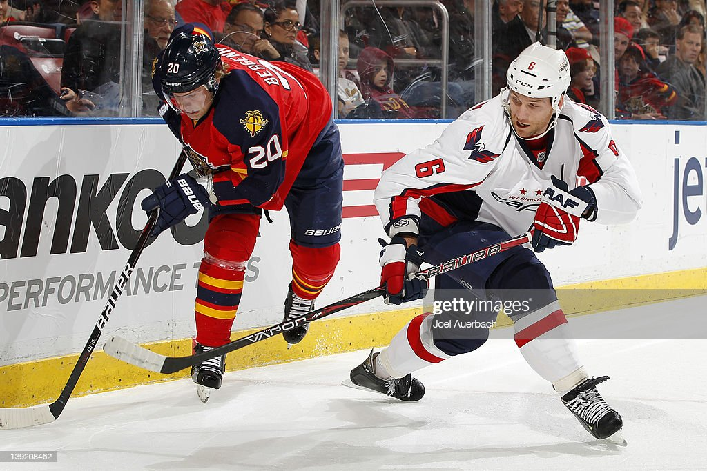 Dennis Wideman #6 of the Washington Capitals and Sean Bergenheim #20 of the Florida Panthers skate after a loose puck on February 17, 2012 at the BankAtlantic Center in Sunrise, Florida.