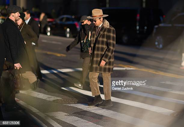 Denny Balmaceda is seen wearing a brown checkered coat brown pants light brown hat and black shoes outside of New York Men's Day during New York...
