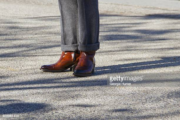 Denny Balmaceda seen wearing grey wool Krammer Stoudt two piece suit and vintage brown tan cowboy ankle boots from Another Man's Treasure on November...