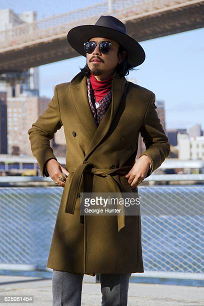 Denny Balmaceda seen wearing grey wool Krammer Stoudt two piece suit red ribbed cotton polo neck turtleneck top by Uniqlo olive green wool Zara coat...