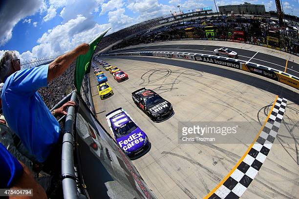 Denny Hamlin driver of the FedEx Cares Toyota and Martin Truex Jr driver of the Furniture Row/Visser Precision Chevrolet lead the field to the green...