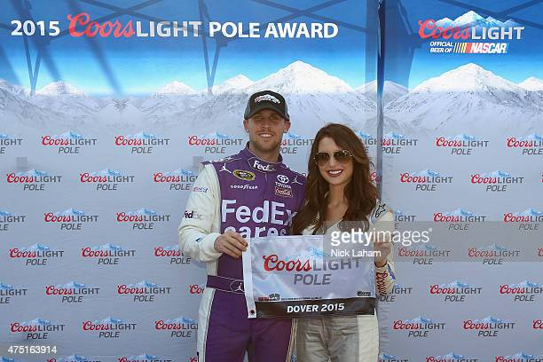 Denny Hamlin driver of the FedEx Cares Toyota left poses with Miss Coors Light Amanda Mertz and the Coors Light Pole Award after qualifying for the...