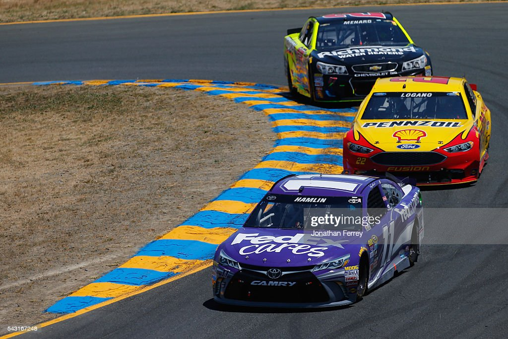 <a gi-track='captionPersonalityLinkClicked' href=/galleries/search?phrase=Denny+Hamlin&family=editorial&specificpeople=504674 ng-click='$event.stopPropagation()'>Denny Hamlin</a>, driver of the #11 FedEx Cares Toyota, races <a gi-track='captionPersonalityLinkClicked' href=/galleries/search?phrase=Joey+Logano&family=editorial&specificpeople=4510426 ng-click='$event.stopPropagation()'>Joey Logano</a>, driver of the #22 Shell Pennzoil Ford, and <a gi-track='captionPersonalityLinkClicked' href=/galleries/search?phrase=Paul+Menard&family=editorial&specificpeople=540271 ng-click='$event.stopPropagation()'>Paul Menard</a>, driver of the #27 Richmond/Menards Chevrolet, during the NASCAR Sprint Cup Series Toyota/Save Mart 350 at Sonoma Raceway on June 26, 2016 in Sonoma, California.