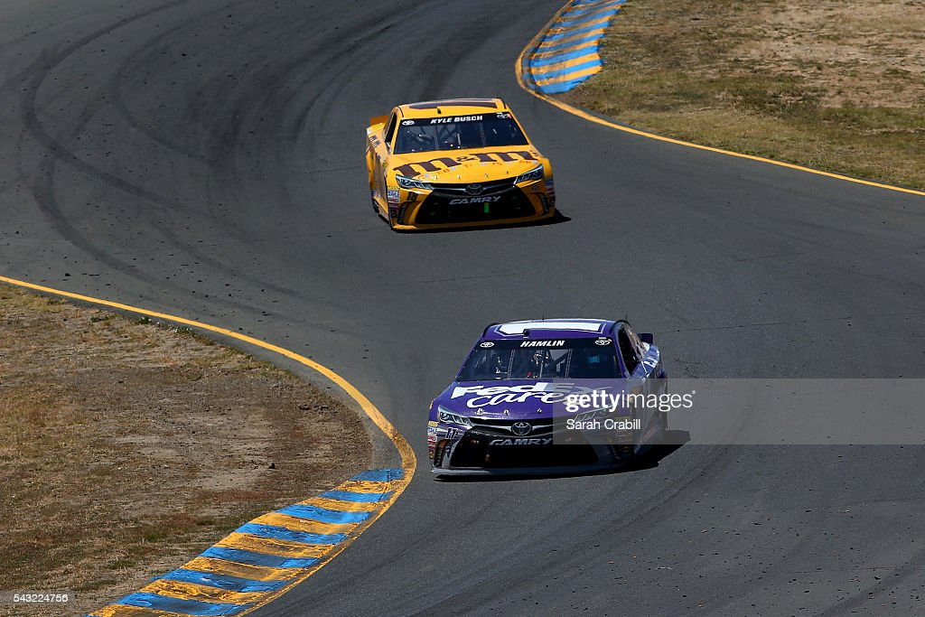 <a gi-track='captionPersonalityLinkClicked' href=/galleries/search?phrase=Denny+Hamlin&family=editorial&specificpeople=504674 ng-click='$event.stopPropagation()'>Denny Hamlin</a>, driver of the #11 FedEx Cares Toyota, races <a gi-track='captionPersonalityLinkClicked' href=/galleries/search?phrase=Kyle+Busch&family=editorial&specificpeople=211123 ng-click='$event.stopPropagation()'>Kyle Busch</a>, driver of the #18 M&M's 75th Anniversary Toyota, during the NASCAR Sprint Cup Series Toyota/Save Mart 350 at Sonoma Raceway on June 26, 2016 in Sonoma, California.