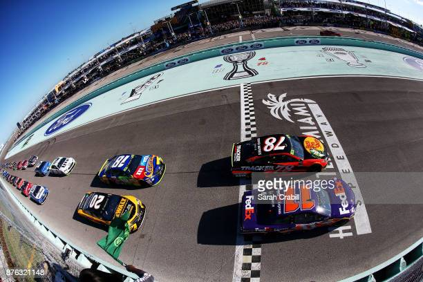 Denny Hamlin driver of the FedEx Express Toyota and Martin Truex Jr driver of the Bass Pro Shops/Tracker Boats Toyota lead the field past the green...