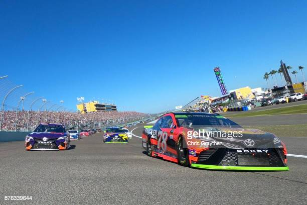 Denny Hamlin driver of the FedEx Express Toyota and Martin Truex Jr driver of the Bass Pro Shops/Tracker Boats Toyota lead the field during pace laps...