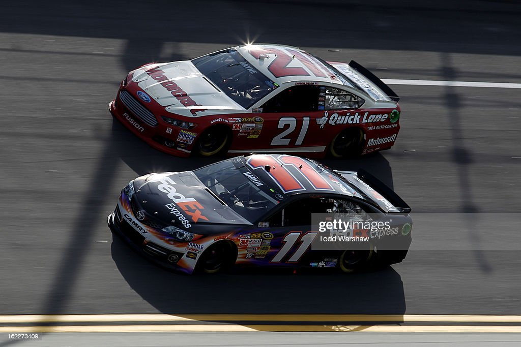 Denny Hamlin, driver of the #11 FedEx Express Toyota, and Trevor Bayne, driver of the #21 Motorcraft/Quick Lane Tire & Auto Center Ford, races side by side during the NASCAR Sprint Cup Series Budweiser Duel 1 at Daytona International Speedway on February 21, 2013 in Daytona Beach, Florida.