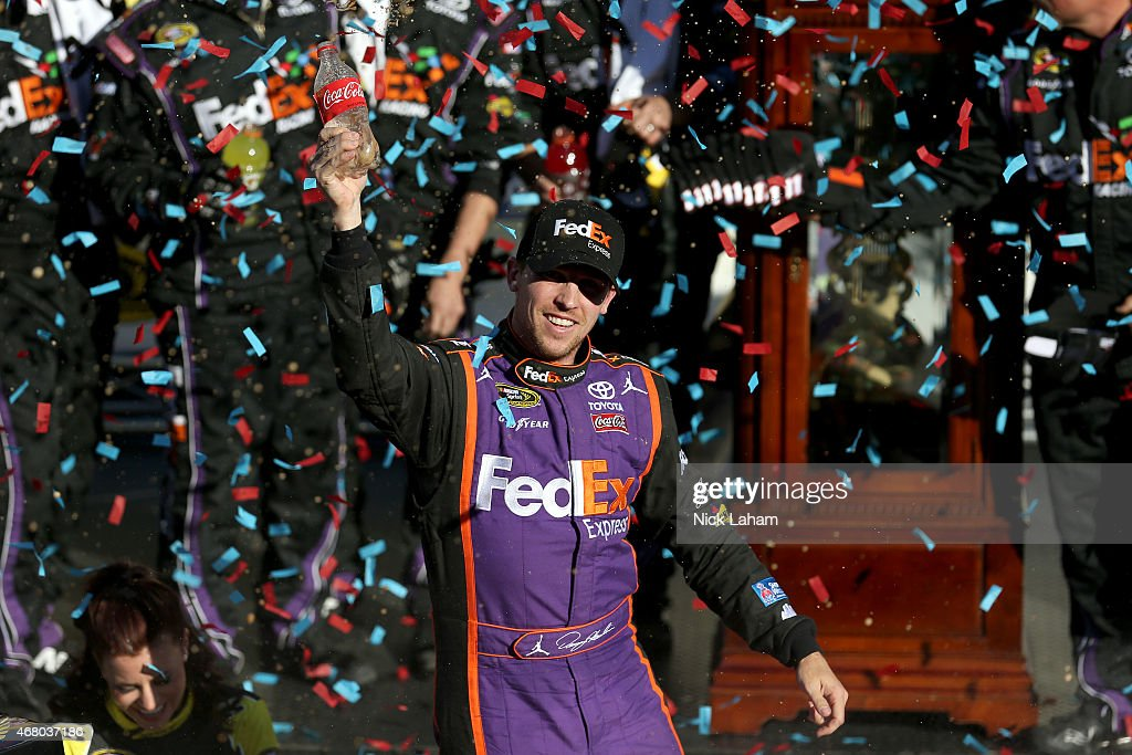 Denny Hamlin, driver of the #11 FedEx Express Toyota, celebrates in Victory Lane after winning the NASCAR Sprint Cup Series STP 500 at Martinsville Speedway on March 29, 2015 in Martinsville, Virginia.