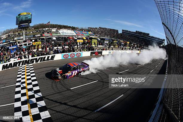 Denny Hamlin driver of the FedEx Express Toyota celebrates with a burnout after winning the NASCAR Sprint Cup Series STP 500 at Martinsville Speedway...