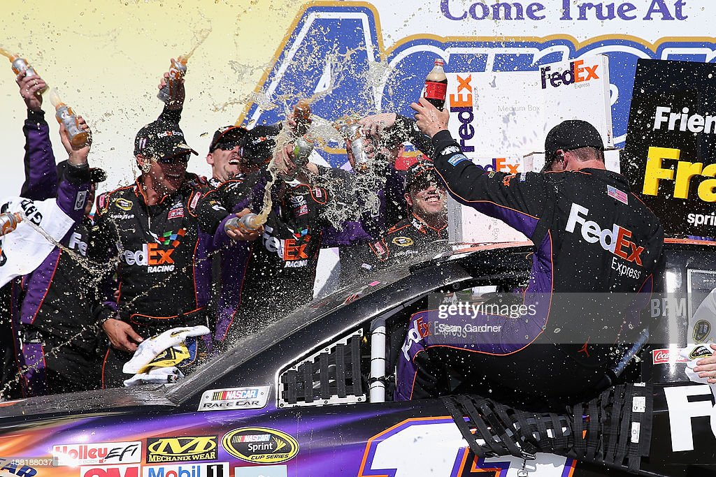 <a gi-track='captionPersonalityLinkClicked' href=/galleries/search?phrase=Denny+Hamlin&family=editorial&specificpeople=504674 ng-click='$event.stopPropagation()'>Denny Hamlin</a>, driver of the #11 FedEx Express Toyota, celebrates with his crew in Victory Lane after winning the NASCAR Sprint Cup Series Aaron's 499 at Talladega Superspeedway on May 4, 2014 in Talladega, Alabama.