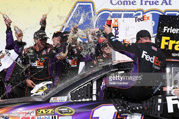 Denny Hamlin driver of the FedEx Express Toyota celebrates with his crew in Victory Lane after winning the NASCAR Sprint Cup Series Aaron's 499 at...