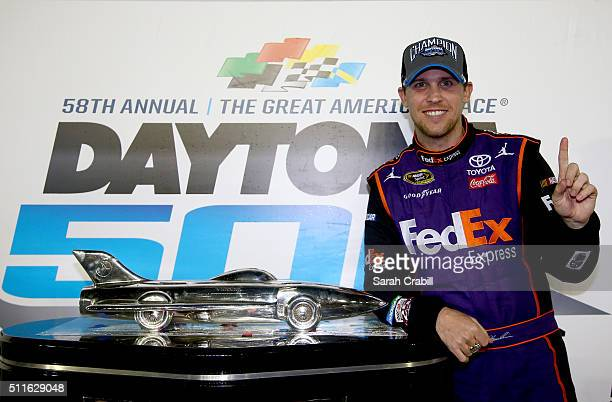 Denny Hamlin driver of the FedEx Express Toyota celebrates with the Harley J Earl Trophy in Victory Lane after winning the NASCAR Sprint Cup Series...