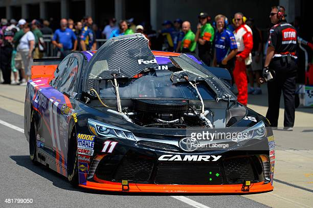 Denny Hamlin driver of the FedEx Express Toyota drives back to the garages after his hood flew up during practice for the NASCAR Sprint Cup Series...