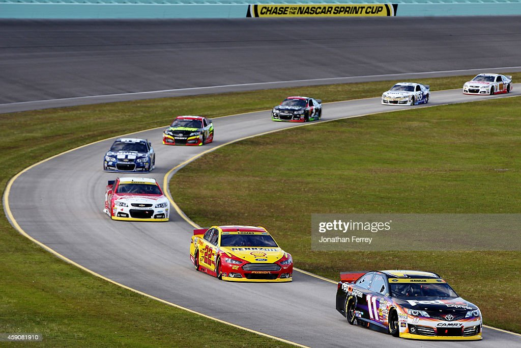 Denny Hamlin driver of the FedEx Express Toyota leads a pack of cars down pit road during the NASCAR Sprint Cup Series Ford EcoBoost 400 at...