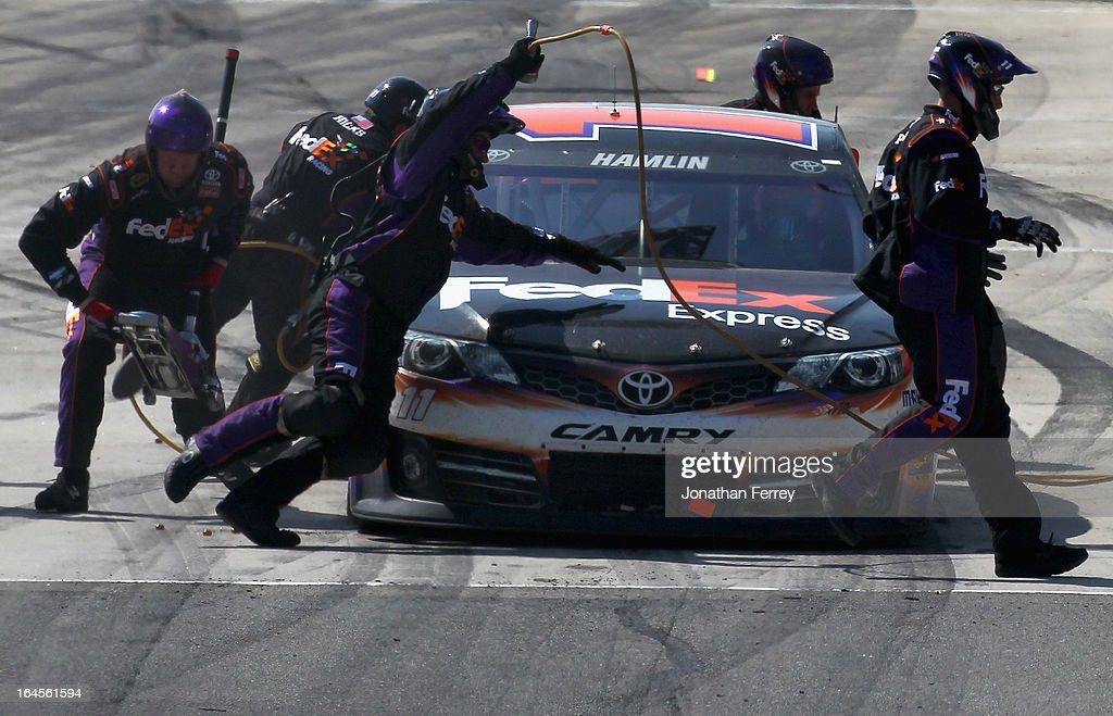 Denny Hamlin, driver of the #11 FedEx Express Toyota, pits during the NASCAR Sprint Cup Series Auto Club 400 at Auto Club Speedway on March 24, 2013 in Fontana, California.