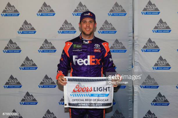Denny Hamlin driver of the FedEx Express Toyota poses with the Coors Light Pole Award after qualifying in the pole position during qualifying for the...