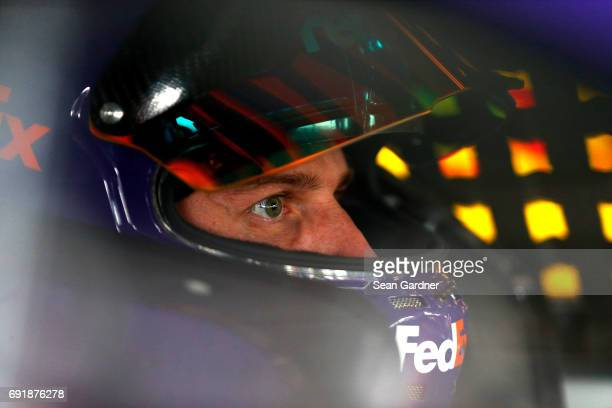 Denny Hamlin driver of the FedEx Express Toyota sits in his car during practice for the Monster Energy NASCAR Cup Series AAA 400 Drive for Autism at...