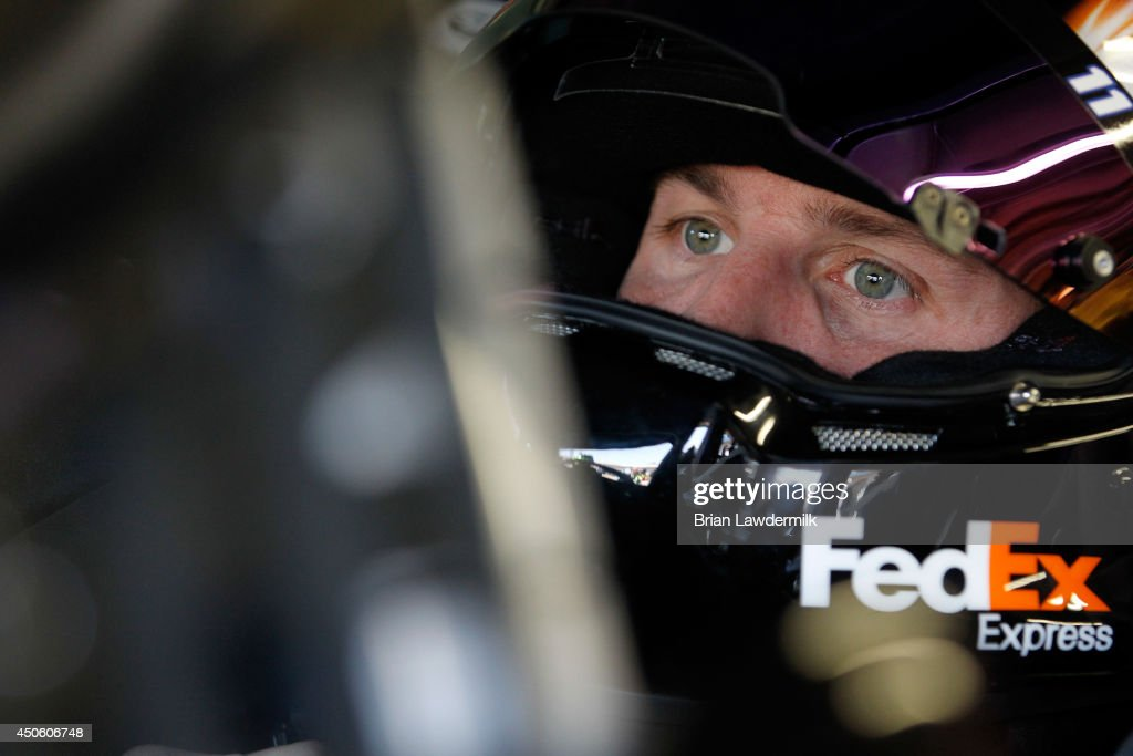 Denny Hamlin, driver of the #11 FedEx Express Toyota, sits in his car in the garage area during practice for the NASCAR Sprint Cup Series Quicken Loans 400 at Michigan International Speedway on June 14, 2014 in Brooklyn, Michigan.