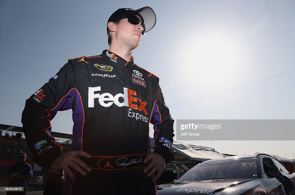 <a gi-track='captionPersonalityLinkClicked' href=/galleries/search?phrase=Denny+Hamlin&family=editorial&specificpeople=504674 ng-click='$event.stopPropagation()'>Denny Hamlin</a>, driver of the #11 FedEx Express Toyota, stands on the grid after qualifying for the NASCAR Sprint Cup Series Auto Club 400 at Auto Club Speedway on March 22, 2013 in Fontana, California.