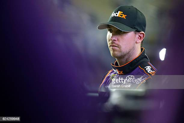Denny Hamlin driver of the FedEx Express Toyota stands on the grid during qualifying for the NASCAR Sprint Cup Series Ford EcoBoost 400 at...