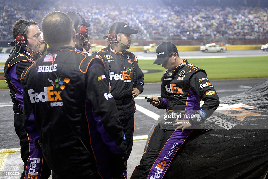 Denny Hamlin (r), driver of the #11 FedEx Express Toyota, stands with crew chief Darian Grubb (m), and teammates during a rain delay during the NASCAR Sprint Cup Series All-Star race at Charlotte Motor Speedway on May 18, 2013 in Concord, North Carolina.