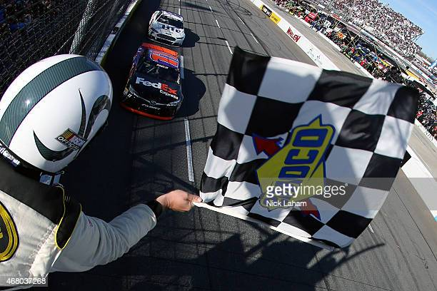 Denny Hamlin driver of the FedEx Express Toyota takes the checkered flag to win the NASCAR Sprint Cup Series STP 500 at Martinsville Speedway on...
