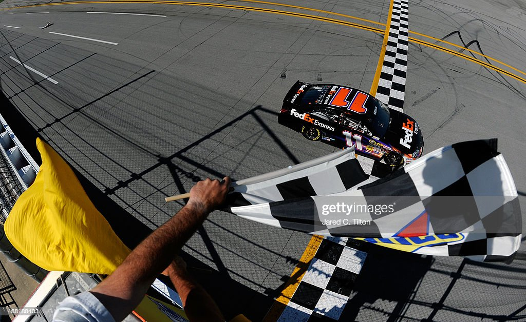 <a gi-track='captionPersonalityLinkClicked' href=/galleries/search?phrase=Denny+Hamlin&family=editorial&specificpeople=504674 ng-click='$event.stopPropagation()'>Denny Hamlin</a>, driver of the #11 FedEx Express Toyota, takes the checkered flag to win the NASCAR Sprint Cup Series Aaron's 499 at Talladega Superspeedway on May 4, 2014 in Talladega, Alabama.