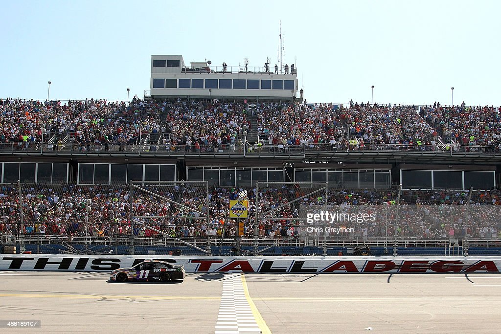 Denny Hamlin, driver of the #11 FedEx Express Toyota, takes the checkered flag to win the NASCAR Sprint Cup Series Aaron's 499 at Talladega Superspeedway on May 4, 2014 in Talladega, Alabama.