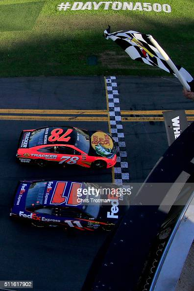 Denny Hamlin driver of the FedEx Express Toyota takes the checkered flag ahead of Martin Truex Jr driver of the Bass Pro Shops/Tracker Boats Toyota...