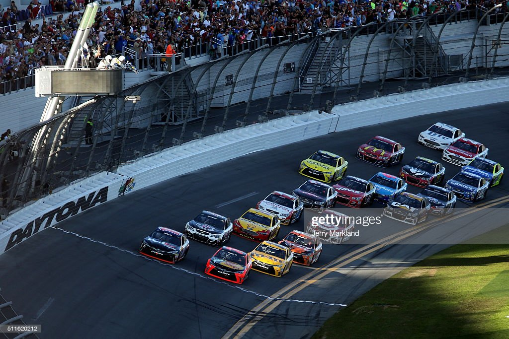Denny Hamlin, driver of the #11 FedEx Express Toyota, takes the checkered flag ahead of Martin Truex Jr., driver of the #78 Bass Pro Shops/Tracker Boats Toyota, to win the NASCAR Sprint Cup Series DAYTONA 500 at Daytona International Speedway on February 21, 2016 in Daytona Beach, Florida.