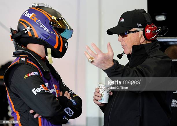 Denny Hamlin driver of the FedEx Express Toyota talks to team owner Joe Gibbs in the garage area during practice for the 57th Annual Daytona 500 at...