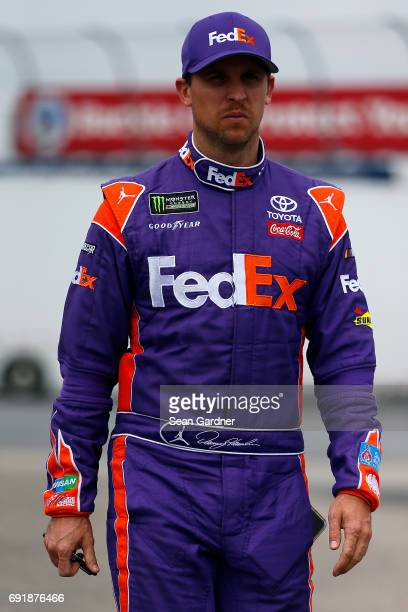 Denny Hamlin driver of the FedEx Express Toyota walks through the garage area during practice for the Monster Energy NASCAR Cup Series AAA 400 Drive...