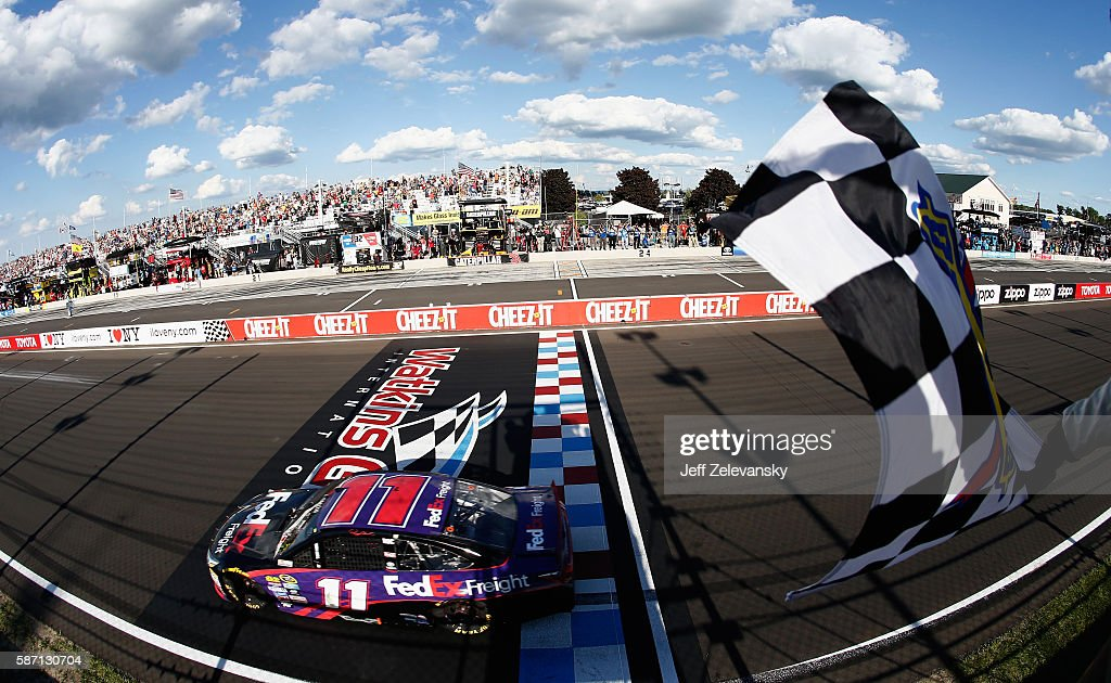 Denny Hamlin, driver of the #11 FedEx Freight Toyota, takes the checkered flag to win the NASCAR Sprint Cup Series Cheez-It 355 at Watkins Glen International on August 7, 2016 in Watkins Glen, New York.