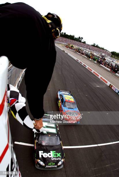 Denny Hamlin driver of the FedEx Ground Chevrolet crosses the finish line ahead of Jeff Gordon driver of the DuPont Chevrolet to win the NASCAR...