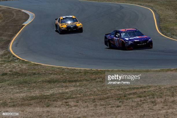 Denny Hamlin driver of the FedEx Ground Toyota and Matt Kenseth driver of the DeWalt Flexvolt Toyota drives during practice for the Monster Energy...