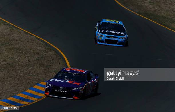 Denny Hamlin driver of the FedEx Ground Toyota and Michael McDowell driver of the KLove Radio Chevrolet drive during practice for the Monster Energy...