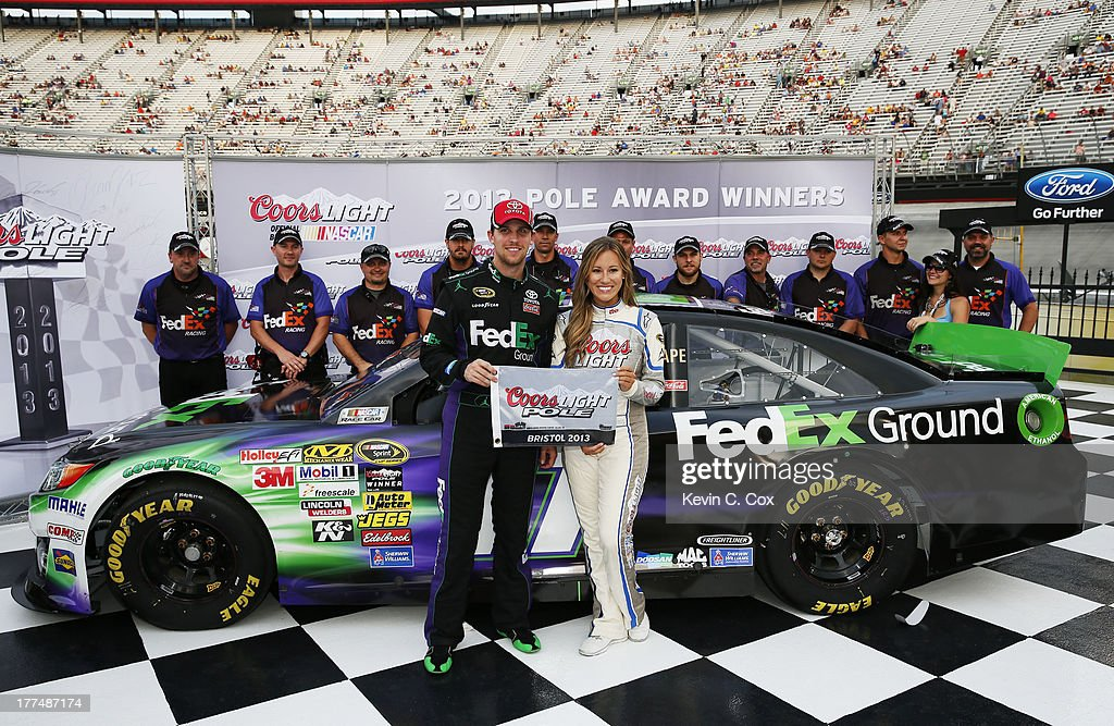 <a gi-track='captionPersonalityLinkClicked' href=/galleries/search?phrase=Denny+Hamlin&family=editorial&specificpeople=504674 ng-click='$event.stopPropagation()'>Denny Hamlin</a>, driver of the #11 FedEx Ground Toyota, and Miss Coors Light Rachel Rupert celebrate with the Coors Light Pole Award after Hamlin qualified for the pole for the NASCAR Sprint Cup Series IRWIN Tools Night Race at Bristol Motor Speedway on August 23, 2013 in Bristol, Tennessee.