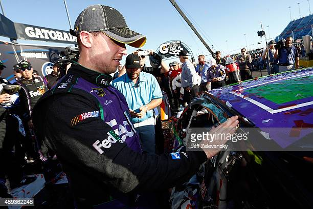 Denny Hamlin driver of the FedEx Ground Toyota applies the race winner sticker to his car in Victory Lane during the NASCAR Sprint Cup Series...
