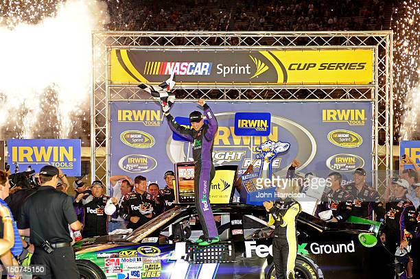 Denny Hamlin driver of the FedEx Ground Toyota celebrates in Victory Lane after winning the NASCAR Sprint Cup Series IRWIN Tools Night Race at...