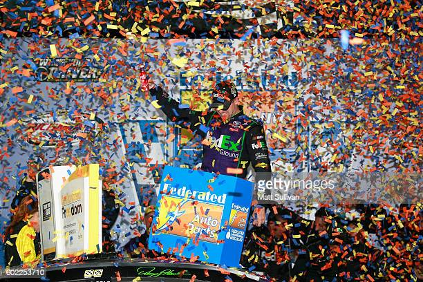 Denny Hamlin driver of the FedEx Ground Toyota celebrates in Victory Lane after winning the NASCAR Sprint Cup Series Federated Auto Parts 400 at...
