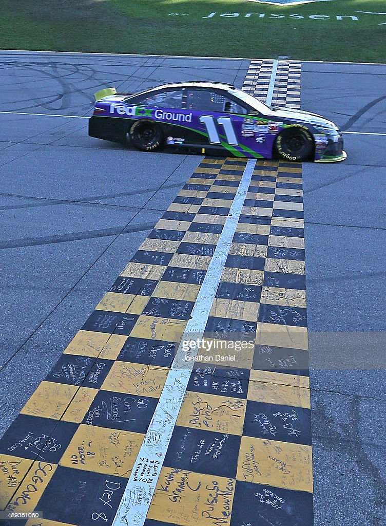 <a gi-track='captionPersonalityLinkClicked' href=/galleries/search?phrase=Denny+Hamlin&family=editorial&specificpeople=504674 ng-click='$event.stopPropagation()'>Denny Hamlin</a>, driver of the #11 FedEx Ground Toyota, crosses the finish-line to win the NASCAR Sprint Cup Series myAFibRisk.com 400 at Chicagoland Speedway on September 20, 2015 in Joliet, Illinois.