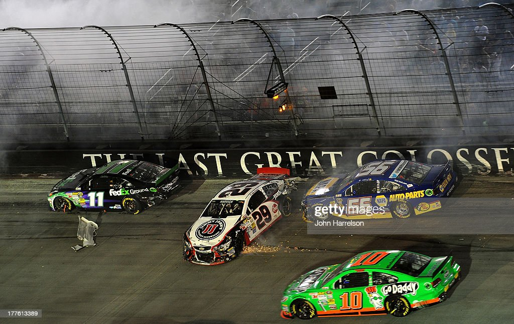 Denny Hamlin, driver of the #11 FedEx Ground Toyota, Kevin Harvick, driver of the #29 Jimmy John's Chevrolet, and Martin Truex Jr., driver of the #56 NAPA Auto Parts Toyota, are involved in an on-track incident during the NASCAR Sprint Cup Series 53rd Annual IRWIN Tools Night Race at Bristol Motor Speedway on August 24, 2013 in Bristol, Tennessee.