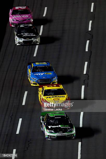 Denny Hamlin driver of the FedEx Ground Toyota leads Joey Logano driver of the ShellPennzoil / Hertz Ford and Ricky Stenhouse Jr driver of the My...