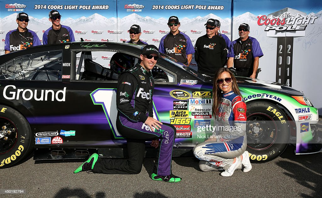 Denny Hamlin, driver of the #11 FedEx Ground Toyota, left, poses with Miss Coors Light Rachel Rupert and the Coors Light Pole Award after qualifying for the pole during qualifying for the NASCAR Sprint Cup Series Pocono 400 at Pocono Raceway on June 6, 2014 in Long Pond, Pennsylvania.