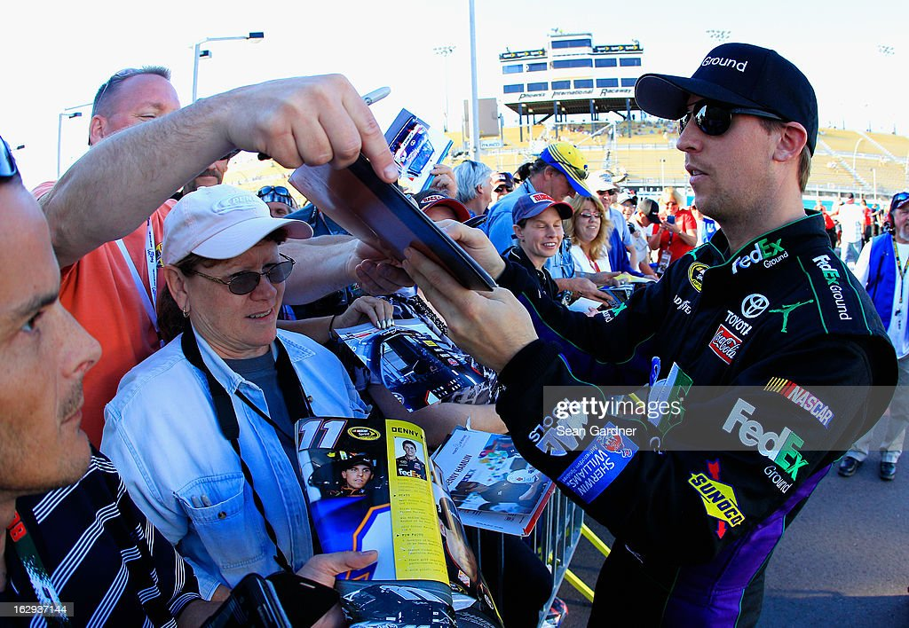 Denny Hamlin, driver of the #11 FedEx Ground Toyota, signs autographs during qualifying for the NASCAR Sprint Cup Series Subway Fresh Fit 500 at Phoenix International Raceway on March 1, 2013 in Avondale, Arizona.