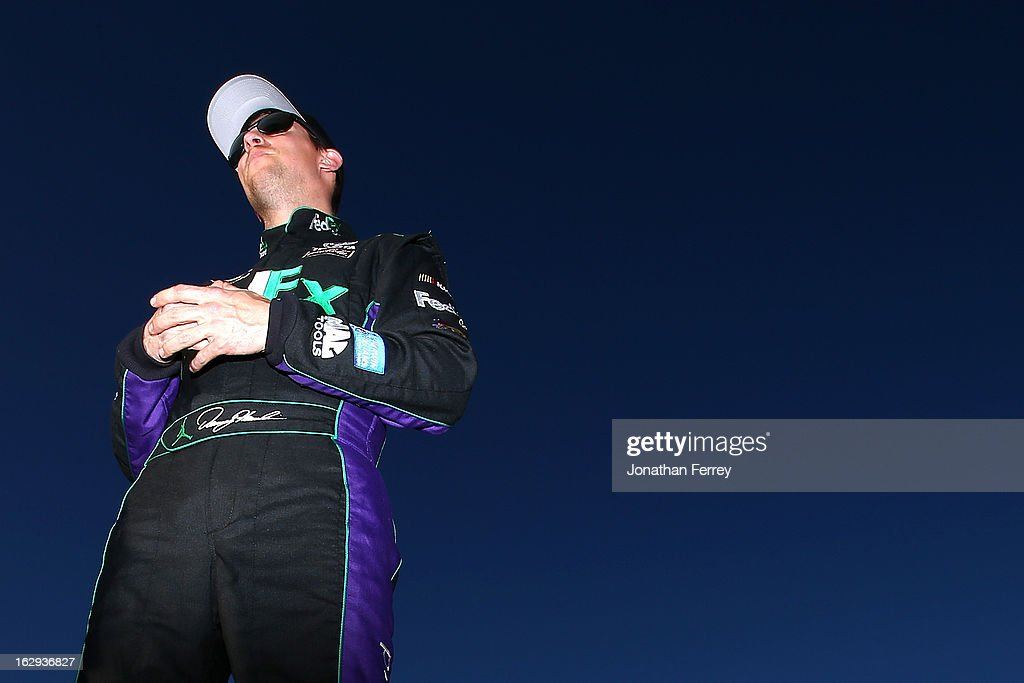 Denny Hamlin, driver of the #11 FedEx Ground Toyota, stands by his car on the grid during qualifying for the NASCAR Sprint Cup Series Subway Fresh Fit 500 at Phoenix International Raceway on March 1, 2013 in Avondale, Arizona.